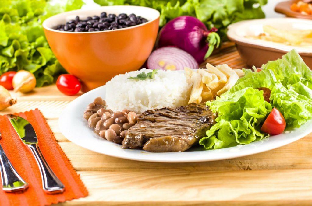 prato com refeição. ao redor talheres, cabelo e uma tigela com feijão preto