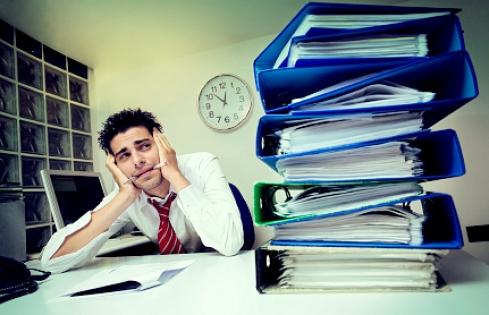 Homem debruçado na mesa com expressão de cansaço e pastas de trabalho acumuladas (franquias on-line baratas)