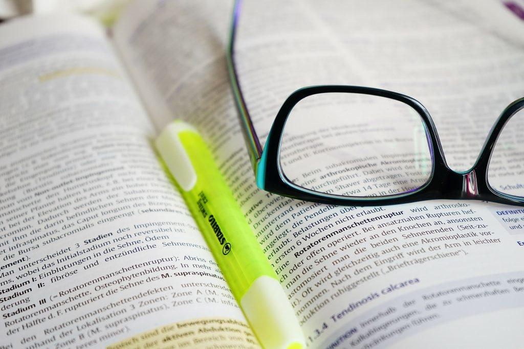 Temos uma imagem focada em um livro aberto. No meio temos um marca texto verde e um par de óculos aberto sobre o livro.