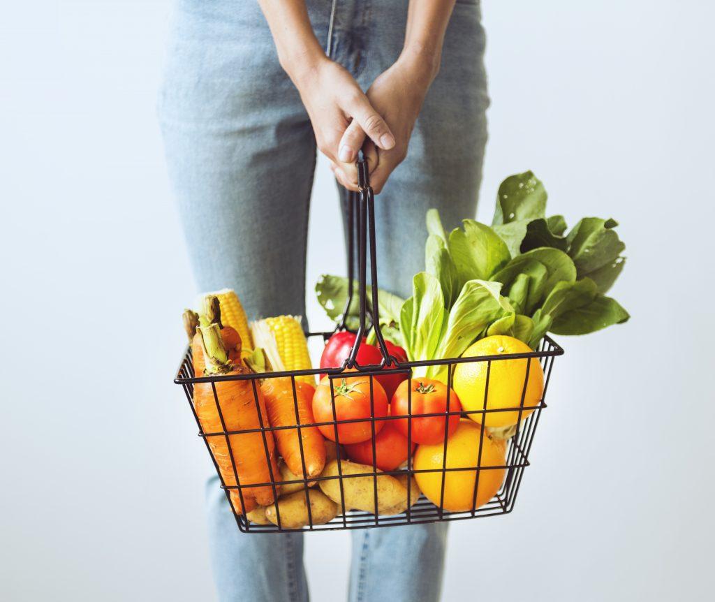 mulher segurando cesta de mercado com legumes e e verduras.