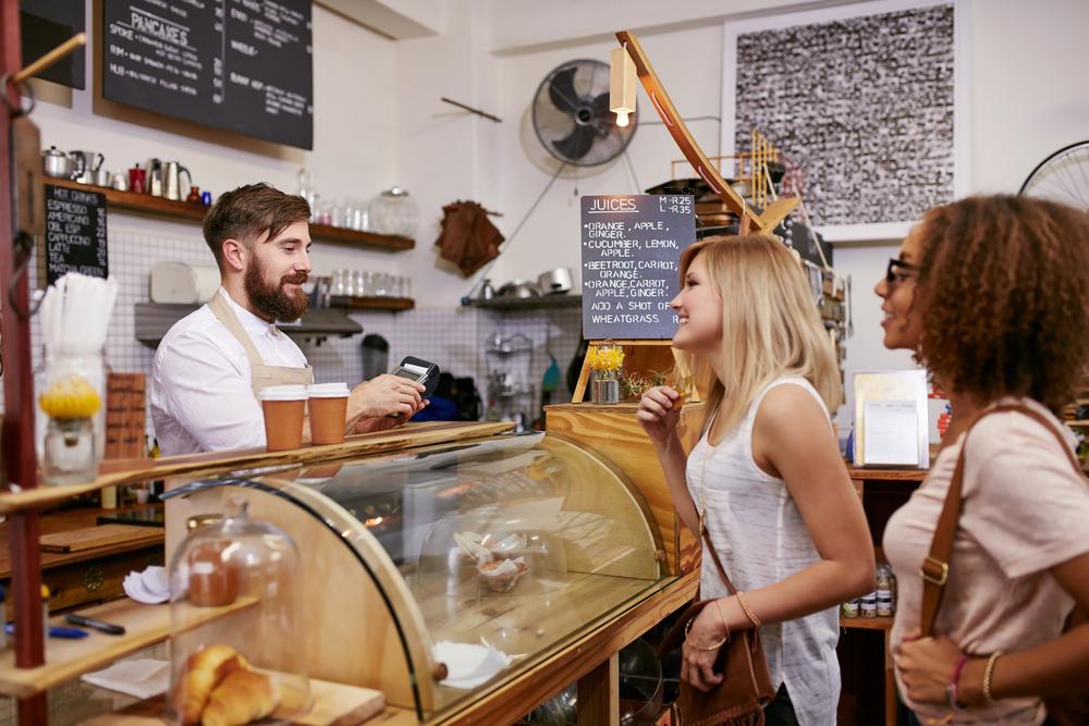 Vemos uma espécie de padaria. O atendente conversa com duas clientes que parecem realizar o pagamento pelo que foi consumido em loja (imagem ilustrativa). Texto: franquia para cidade pequena.