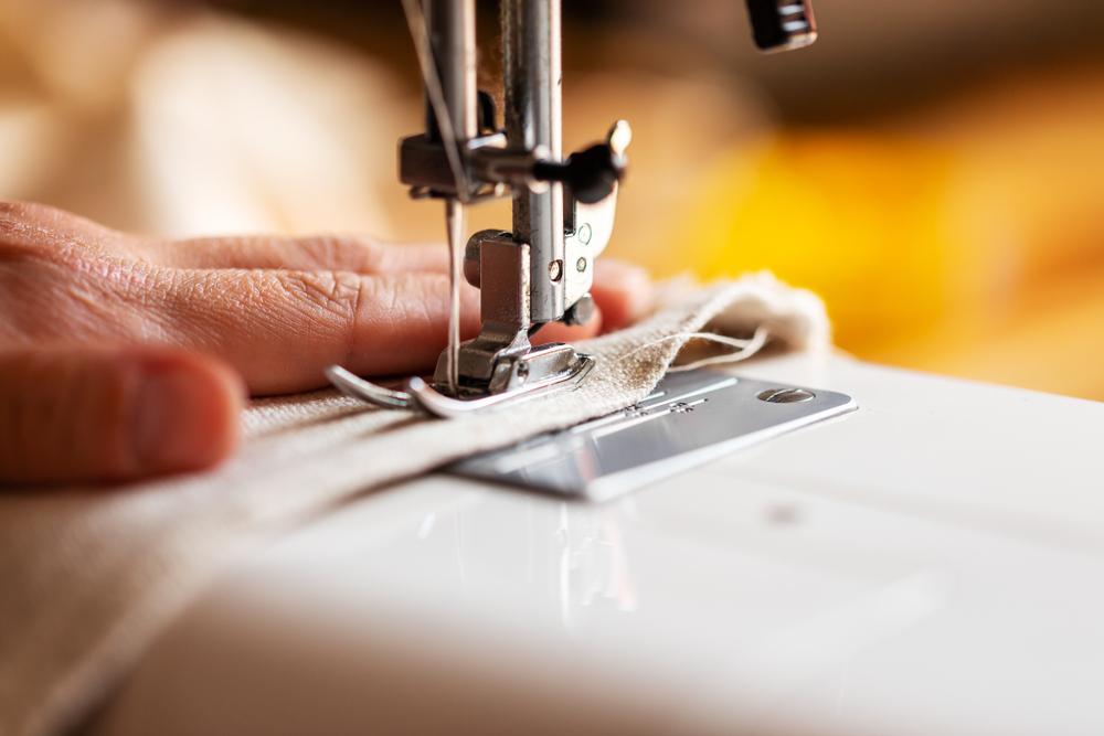 Close em uma mão trabalhando na máquina de costura. Ilustração do texto o que é franquia.