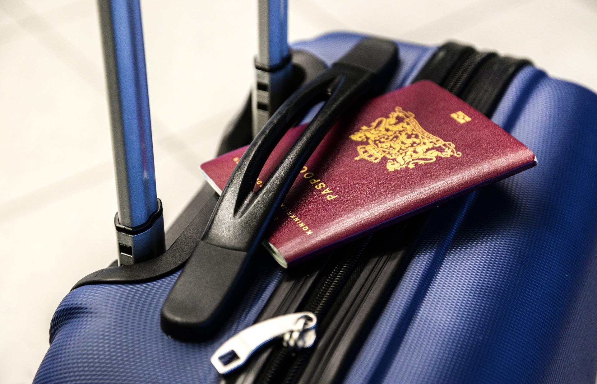 Imagem de uma mala e um passaporte. Imagem ilustrativa texto como montar uma agência de viagens online.
