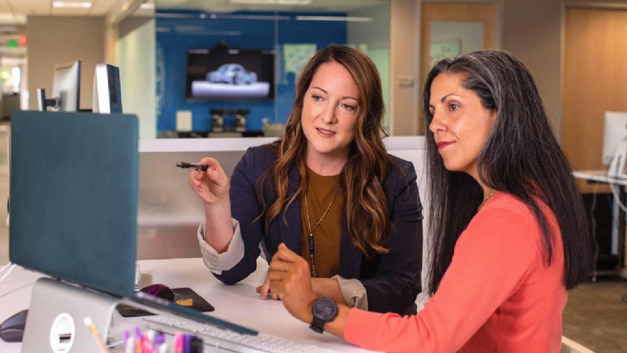 Imagem de duas mulheres olhando para um computador em um escritório. Imagem ilustrativa texto como montar uma agência de viagens online.