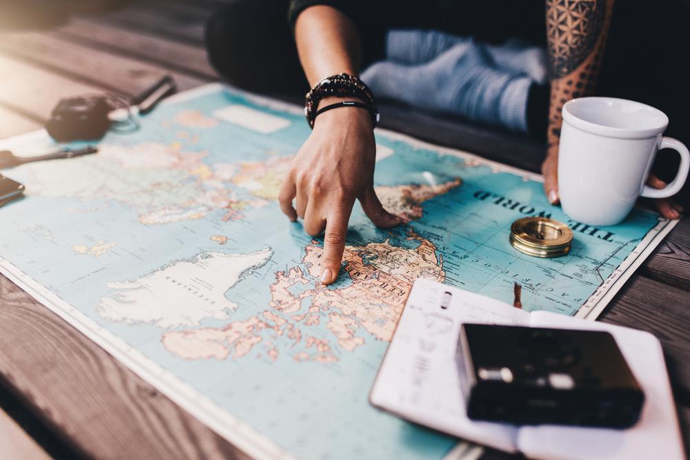 Mão de uma pessoa apontando para um mapa que está aberto sobre uma mesa. É possível visualizar uma xícara branca, caderno, bússola dourada e um dispositivo na cor preta.