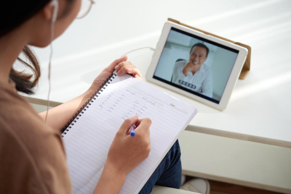 Mulher sentada assistindo a uma aula em um tablet, enquanto anota o conteúdo em um caderno. Ilustração do texto sobre circular de oferta de franquia.