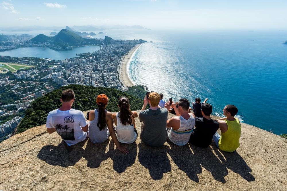 Vemos um grupo de jovens, entre homens e mulheres, na Pedra do Telégrafo, no Rio de Janeiro (imagem ilustrativa).