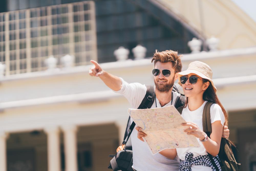 """Vemos um casal (homem e mulher) em um ponto turístico. Vestidos quase """"à caráter"""" – chapéu contra o sol, bolsa, câmeras fotográficas, o homem aponta para uma direção enquanto a mulher, que tem um mapa nas mãos, olha na mesma direção após consultar o material (imagem ilustrativa)."""
