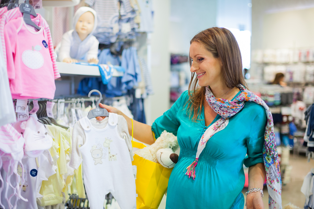 moça olhando roupas bebe loja