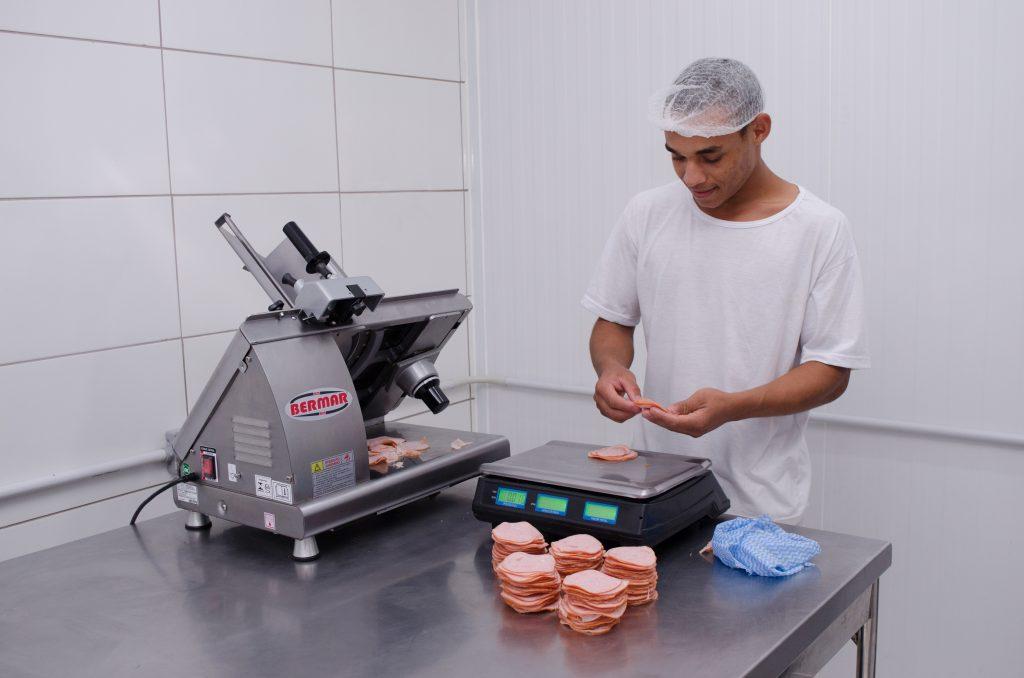 homem trabalhando no porcionamento de ingredientes cozinha central