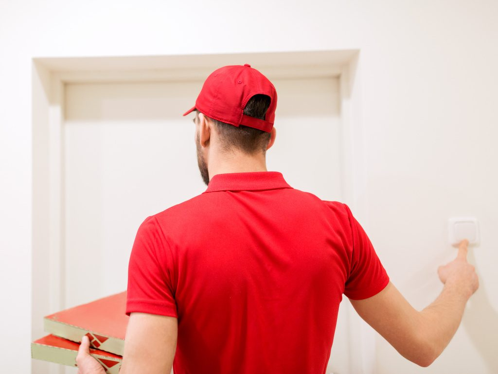 entregador batendo na porta de uma casa para fazer a entrega de pizza delivery