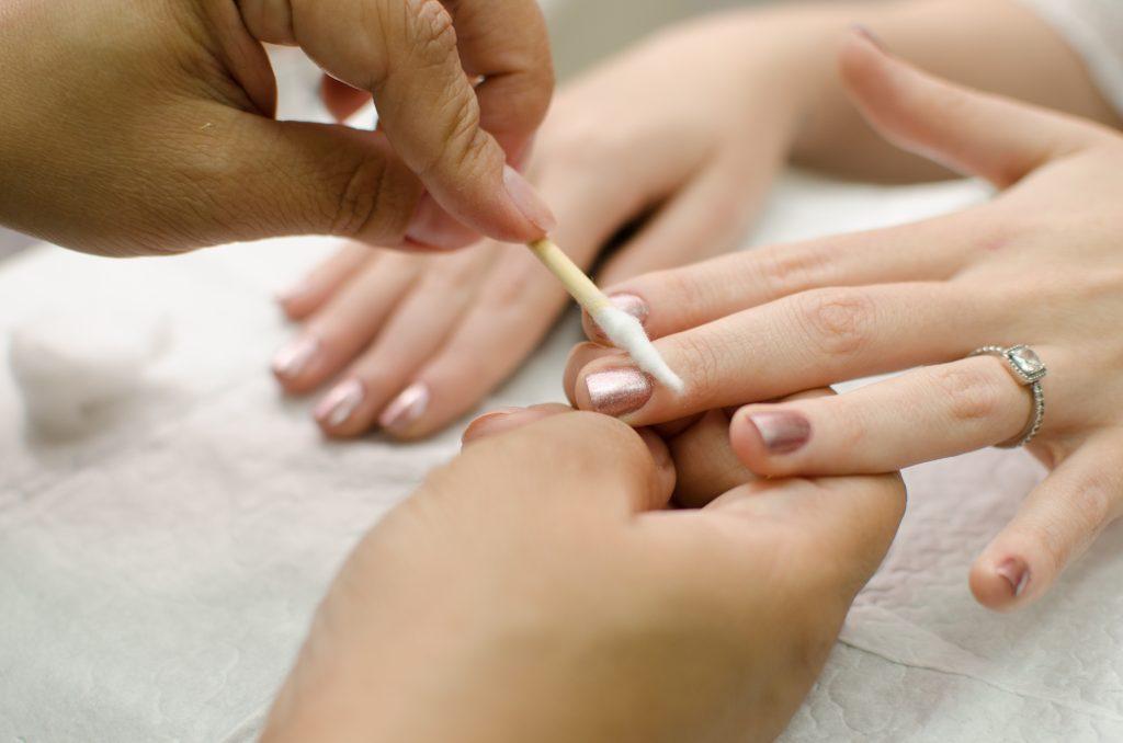 manicure passando esmalte na mão da cliente