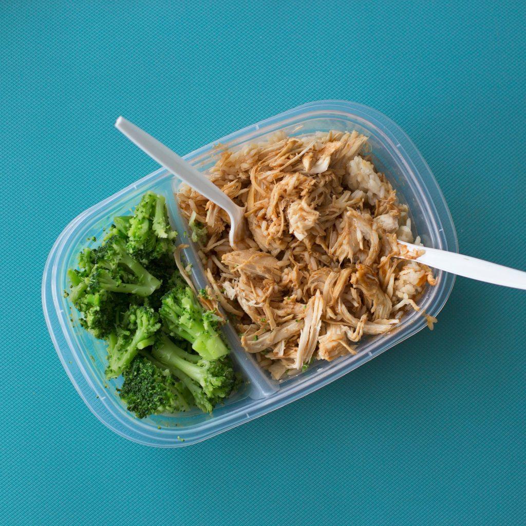 Vemos em um fundo azul um prato de frango desfiado com brócolis cozidos. Uma marmita saudável e um dos mercados para empreender.