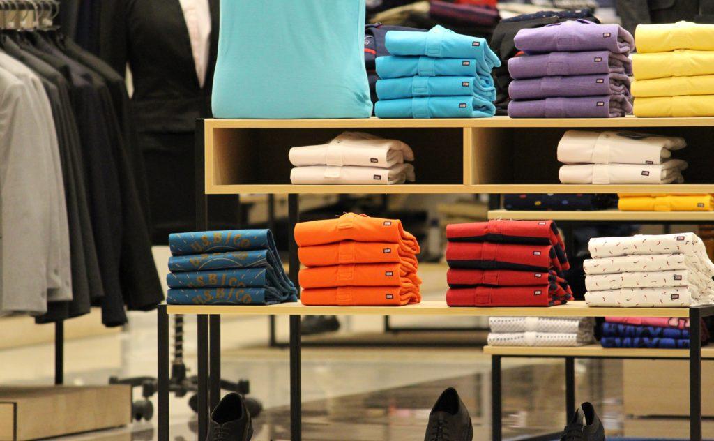 Prateleiras com roupas coloridas e organizadas por cor