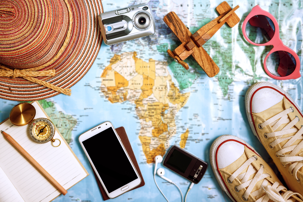 Imagem de um mapa com itens sobre ele. É possível observar um par de ténis, celular, dispositivo de música, fones de ouvido, caderno, lápis, bússula, pequeno avião de madeira, chapéu, câmera fotográfica e um óculos de sol. Ilustração do texto mini franquias 2021.