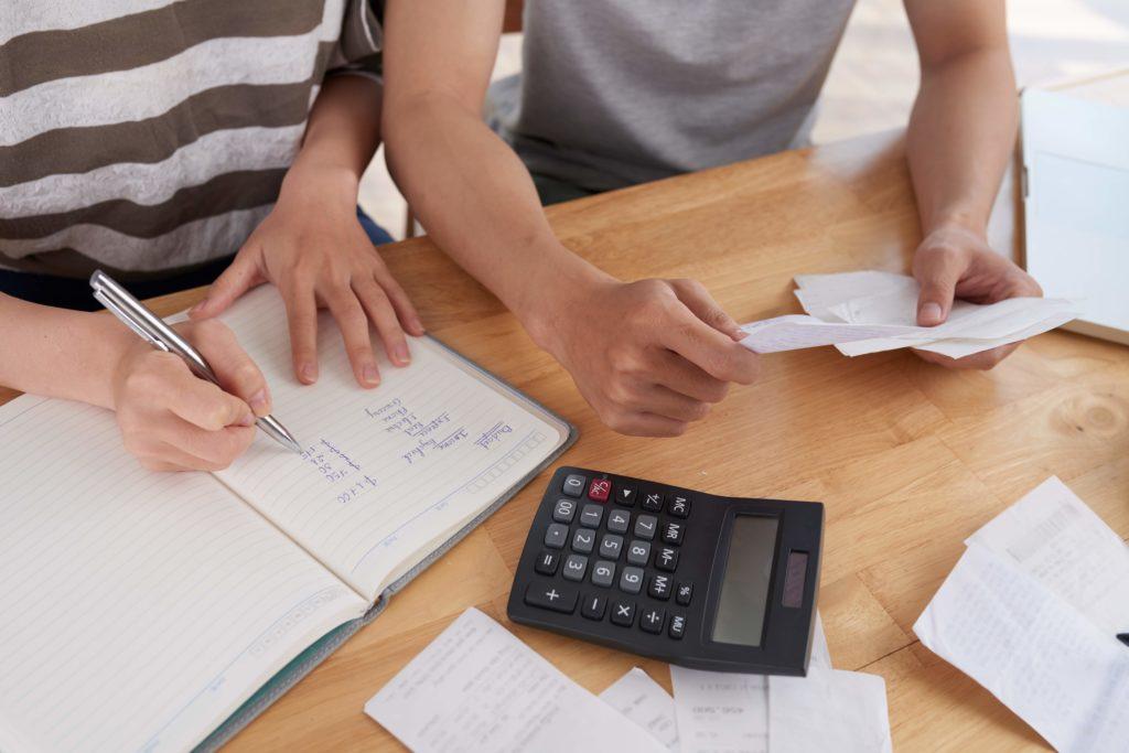 Pessoas analisando e fazendo conta de gastos