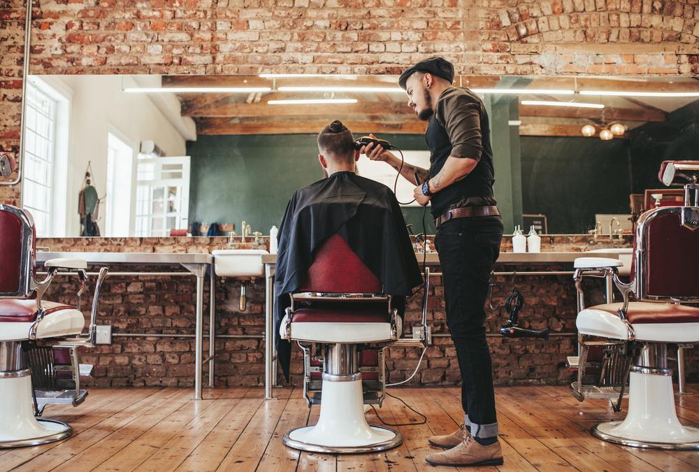 homem em barbearia cortando cabelo de cliente