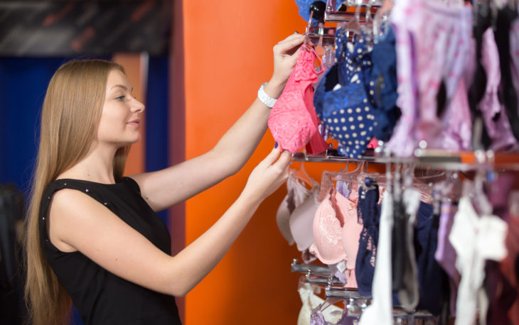 Portrait of smiling young beautiful woman shopping, standing in the mall, looking at lingerie on hanger, choosing new pink underwear