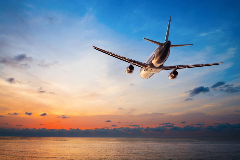 Avião voando sobre o oceano durante o pôr do sol