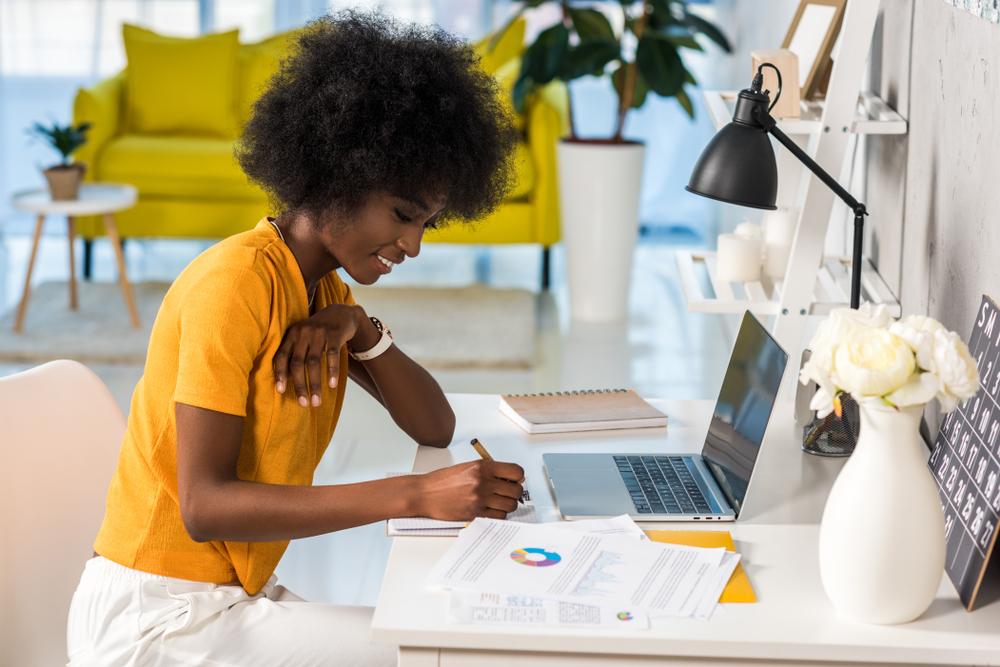 Moça usando blusa amarela e calça branca em um mesa com computador, e papéis, fazendo anotações.
