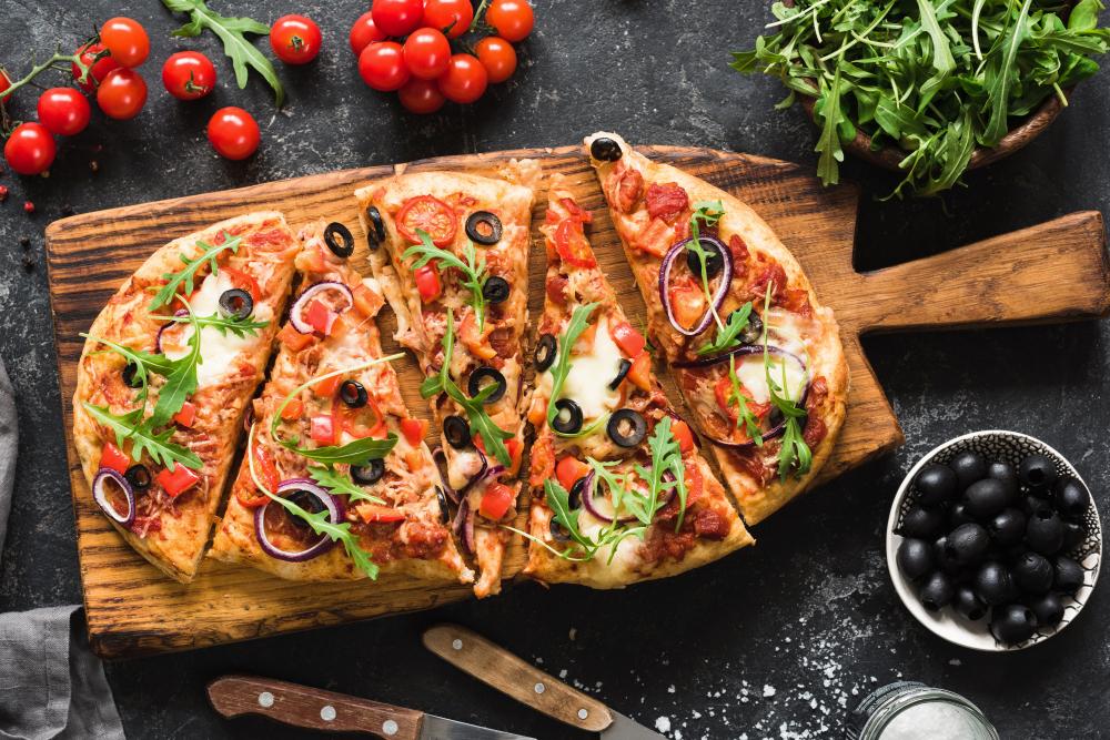 pizza fatiada em cima de uma tabua de madeira