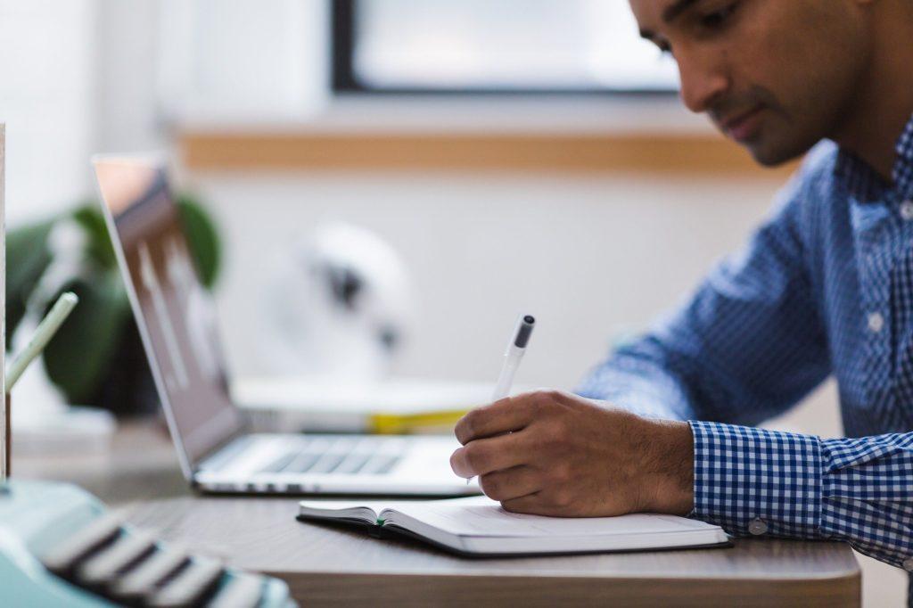 homem sentando escrevendo em um cadernos com um notbook em sua frente.