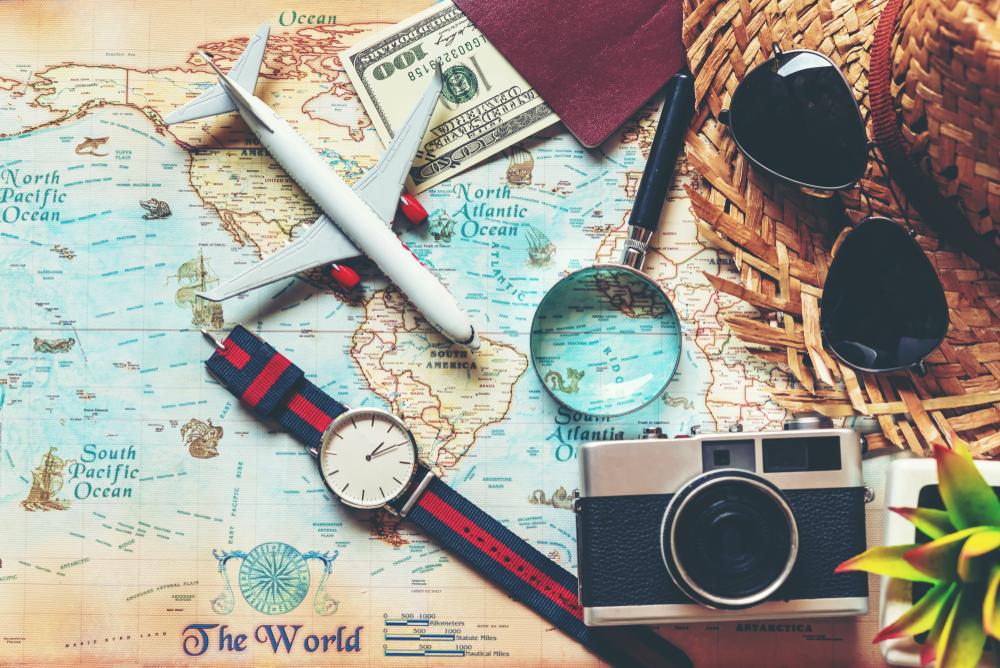 Vemos um mapa-múndi ao fundo. Sobre o objetos temos: um chapéu de palha, um óculos de sol, um passaporte e uma nota de 100 dólares; uma lupa, uma câmera fotográfica, um relógio e uma miniatura de avião (imagem ilustrativa). Texto: microfranquias 2021.