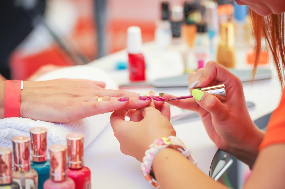 Imagem de uma moça fazendo unha. Imagem ilustrativa texto franquia esmalteria quanto custa.