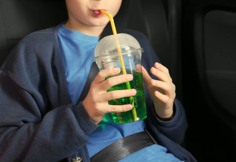 criança bebendo suco dentro de um carro