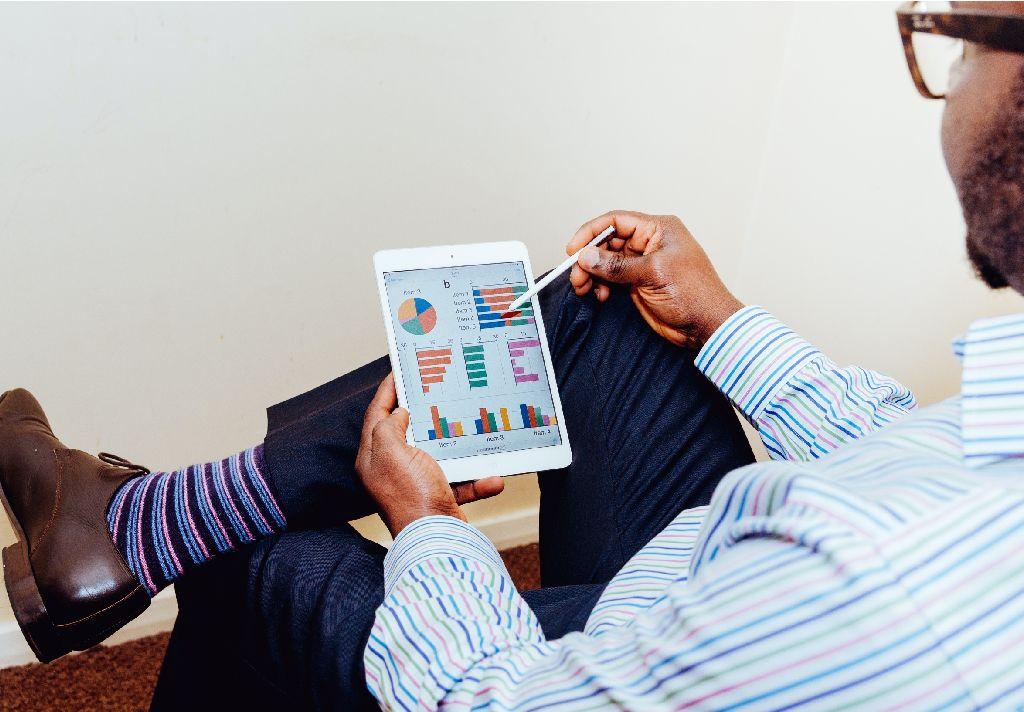 Vemos um homem sentado, segurando um tablet com vários gráficos na tela. Eles os analisa (imagem ilustrativa). Texto: contrato de franquia.