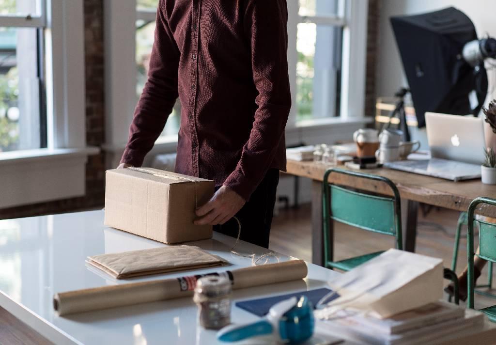 Vemos uma espécie de estúdio ou ateliê. Sobre as mesas temos computador, papel kraft, barbante, grampeador, sacolas etc.  No primeiro plano da imagem vemos um homem empacotando sua mercadora (imagem ilustrativa). Texto: franquias mais lucrativas 2021.
