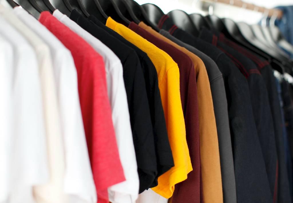 Vemos algumas camisetas de várias cores em cabides (imagem ilustrativa). Texto: franquias baratas de roupas.