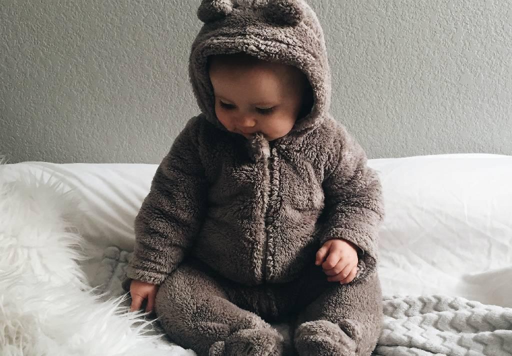 Vemos um bebê trajando uma roupa de ursinho.