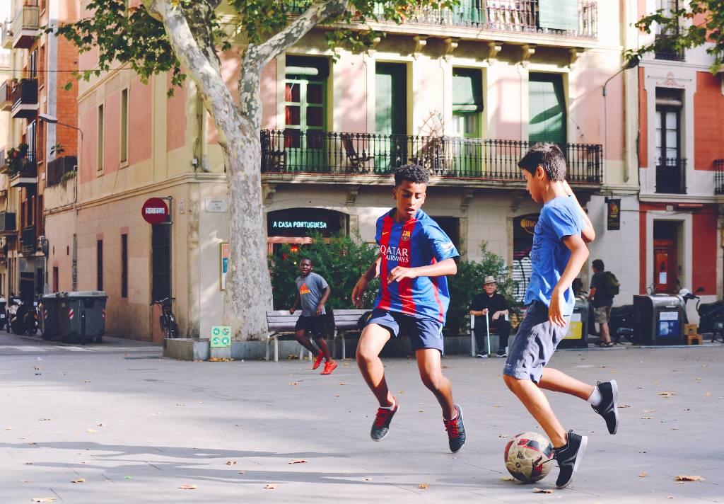 Vemos dois adolescentes jogando futebol. Um deles veste uma camiseta de time profissional (imagem ilustrativa). Texto: franquias baratas de roupas.