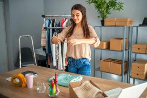Franquias de roupas on-line: Jovem fotografando uma peça para vender