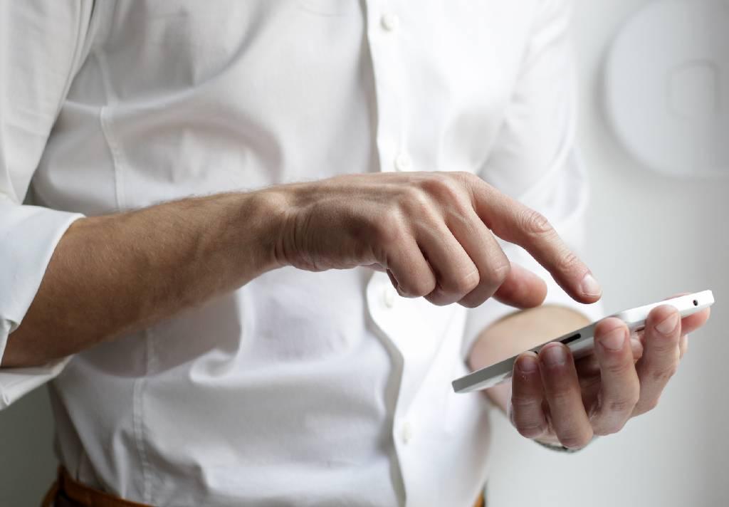 Vemos um homem, trajando camiseta social branca. A imagem nos mostra apenas suas mãos, que seguram um celular, enquanto ele o utiliza (imagem ilustrativa).
