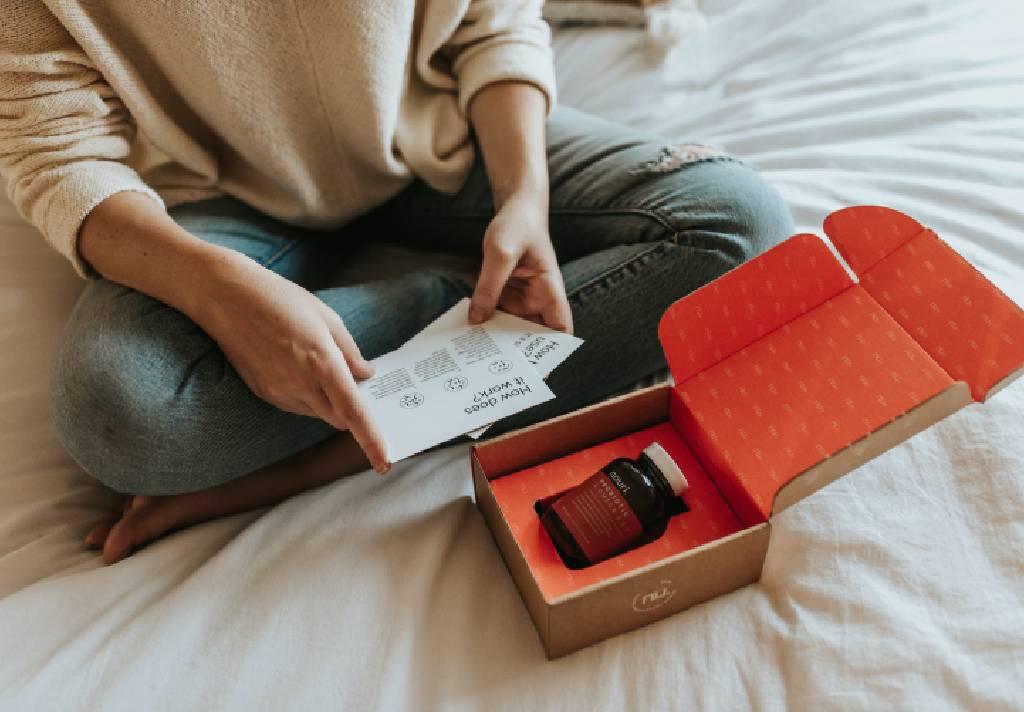 Vemos uma mulher sentada em um colchão. Em perspectiva temos uma caixa que acaba de ser aberta. Ela segura algo que parece ser as instruções de uso (imagem ilustrativa). Texto: franquias mais lucrativas 2021.