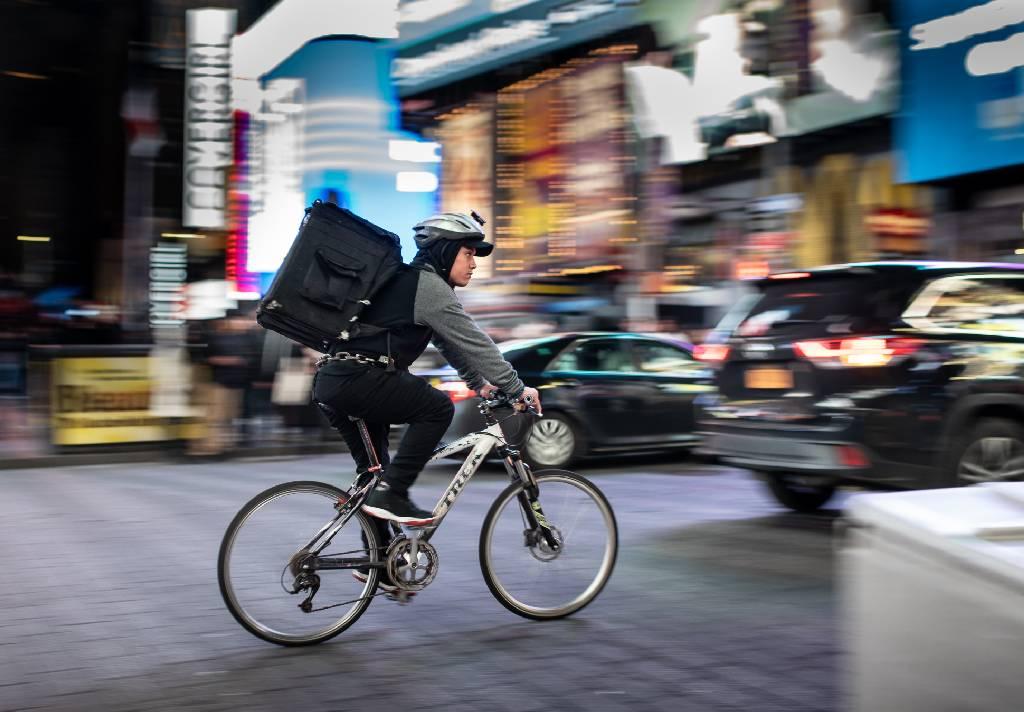 Vemos uma foto de um local movimentado com prédios e carros. Em foco temos um homem em uma bicicleta levando às costas uma grande mochila, comum para quem realiza serviços de entrega (imagem ilustrativa). Texto: franquias mais lucrativas 2021.