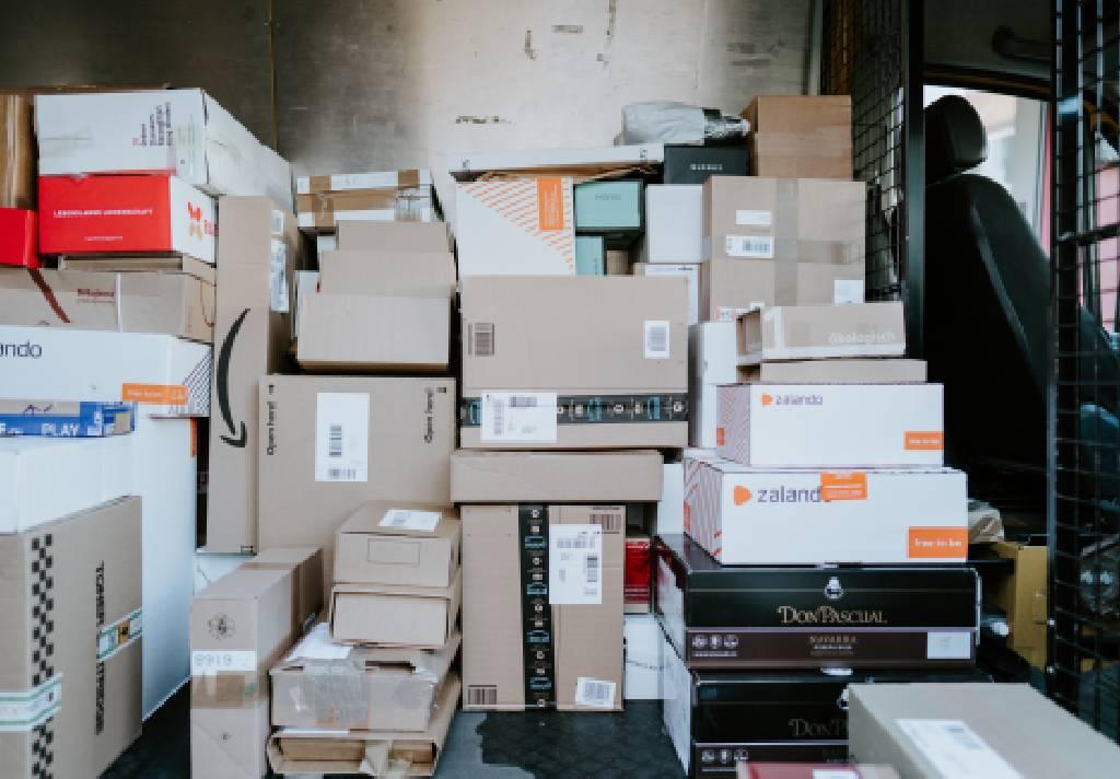 Vemos, em uma van de entrega, diversas caixas de produtos comprados pela internet (imagem ilustrativa).