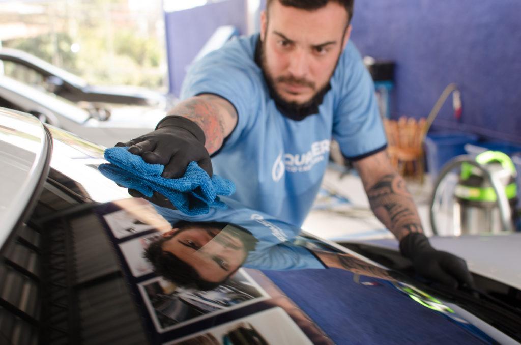 Homem com camisa azul limpando o carro com técnica Acquazero. Imagem do texto mini franquias 2021.