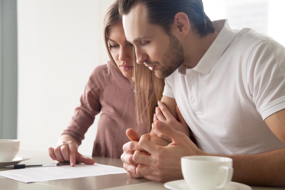 Vemos um casal analisando um contrato.