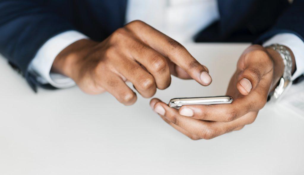 Vemos as mão de um homem que faz alguma coisa em seu celular. É possível notar que ele usa terno e gravata.