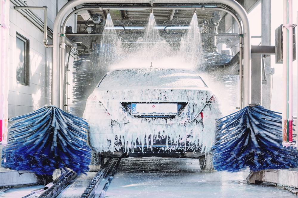 carro sendo lavado na franquia de lava rápido com jatos de água