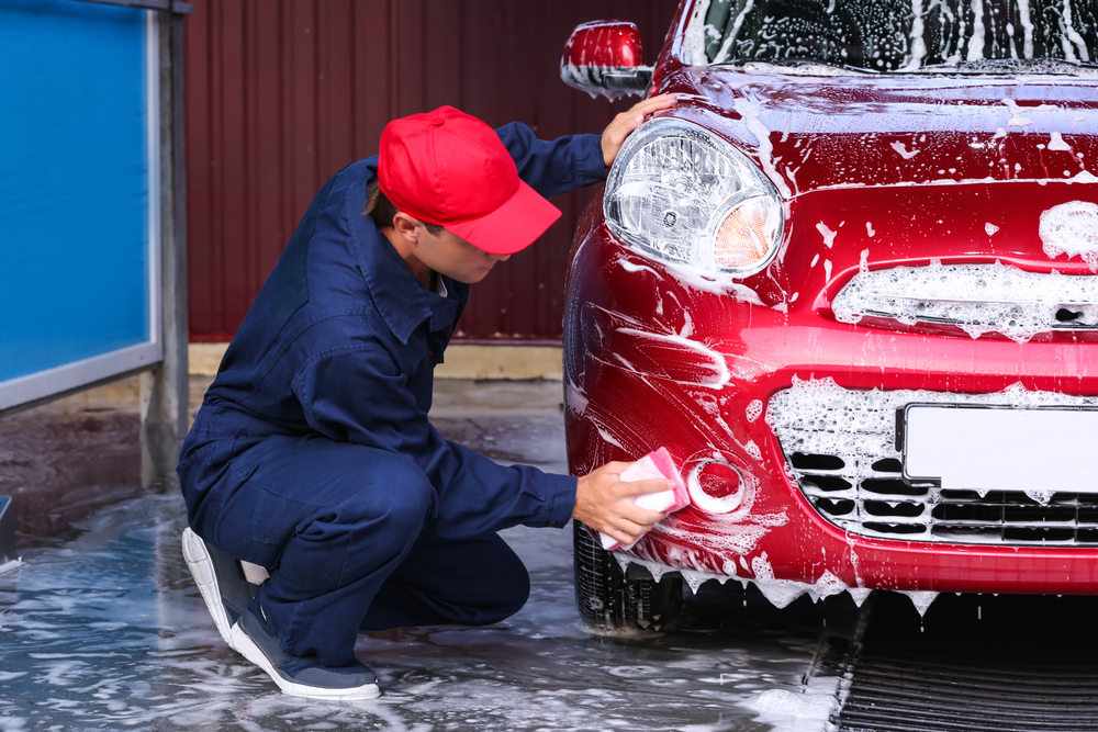 homem lavando um carro com água e sabão
