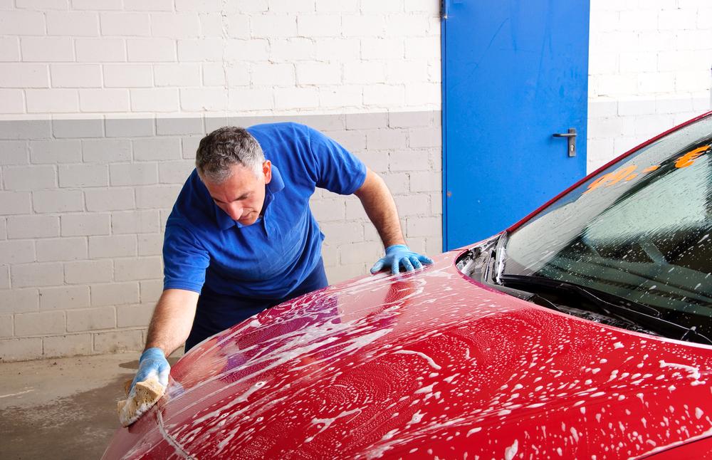 carro sendo lavado na franquia de lava rápido com água e sabão