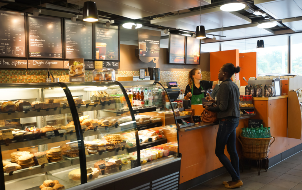 Visão interna de uma unidade Starbucks. É possível observar várias opções de lanches na vitrine e uma funcionária atendendo uma cliente. Ilustração do texto franquia Starbucks.