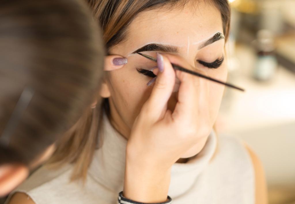 mulher fazendo as sobrancelhas ilustrativo texto franquias de manicure e pedicure express