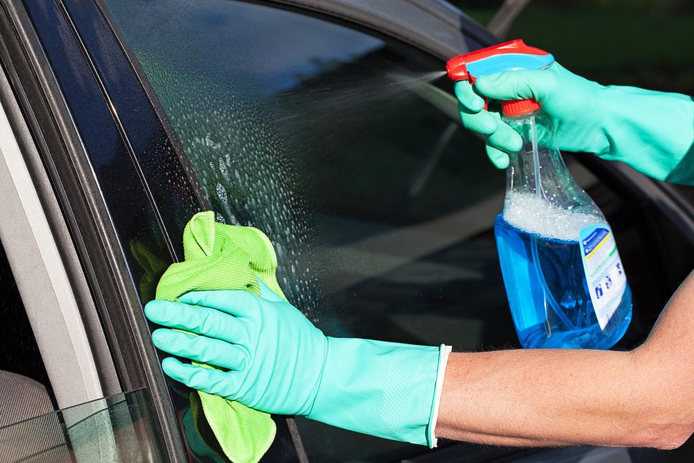 Lava rápido a seco: responsável fazendo a limpeza de um vidro