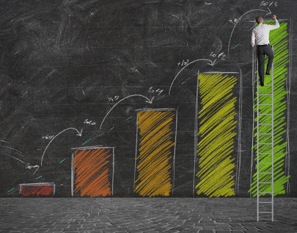 Vemos um um quadro escolar preto, fosco. Nele está desenhado um gráficos, com colunas nas cores vermelho, laranja escuro, laranja claro, amarelo e verde. A cor corresponde à progressão de crescimento das colunas no gráfico. Na extrema direita, onde está a coluna verde, vemos um homem no topo de uma escada. É possível ver um +8% grafado entre a coluna amarela e a verde (imagem ilustrativa).