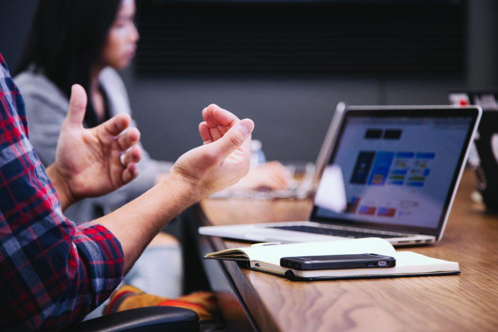 Mãos de um homem com blusa xadrez gesticulando e ao fundo vemos uma muher com roupa cinza. Na mesa de madeira podemos observar um notebook ligado, um caderno e célula. Ilustração do texto mini franquias 2021.